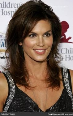 Medium to long length with layers. Medium brown. Like her cut and color!