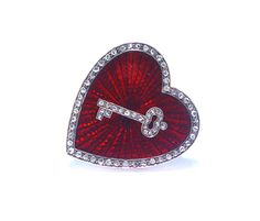 An Edwardian jeweled and enameled brooch In the form of a heart enameled translucent scarlet over a sunburst guillochage emanating from a diamond set key, bordered with rose diamonds, the reverse with a glass covered compartment. The brooch is a rebus reading 'key to my heart forever', the diamonds being emblematic of eternity. English, circa 1905.