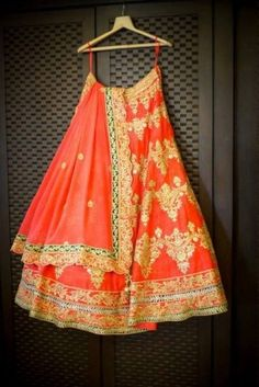 Coral and gold bridal lehenga with a flash of emerald green. Lovely!
