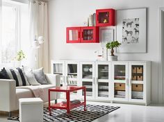 A white living room with a two-seat sofa and a low storage combination with open and closed storage. Combined with a coffee table on castors and wall cabinets with glass doors, all in red.