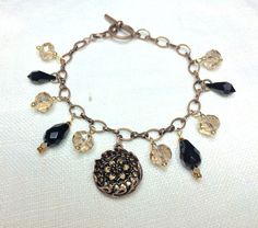 Antique button charm bracelet showcasing an antique button and Swarovski crystals in black and champagne.
