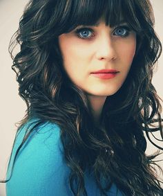 Zooey Deschanel with long, thick, curled hair and heavy bangs.  Her eyes are SO BLUE in this picture!  They match her shirt!