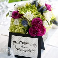 """Hydrangeas, dahlias, and blue thistle made for understated centerpieces that paired well with blue-and-green menu cards, completing the couple's """"New England vintage"""" meets """"modern"""" style."""