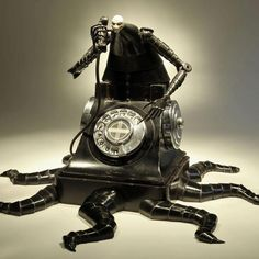 """Artist:Greg Brotherton  Listening In  2011  Size: 12 """" x 18 """" x 18 """"  Materials: Welded steel, cast pewter, payphone dial, parts from a beer tap, concrete"""