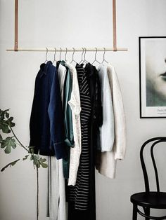 leather and wood hanging clothes rail.
