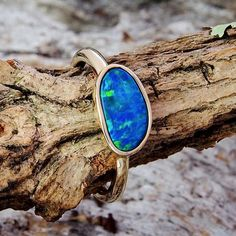 9ct yellow gold ring bezel set with a blue freeform oval doublet opal featuring vibrant green and aquamarine highlights