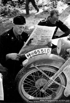 Members of the 3rd SS Panzer Division Totenkopf (Skull and Crossbones) catching up with the news.