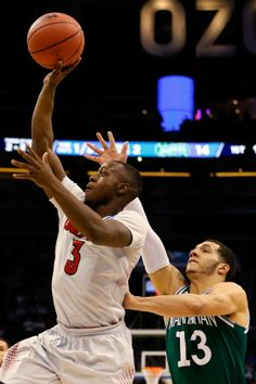 Chris Jones #3 of the Louisville Cardinals shoots against Emmy Andujar #13 of the Manhattan Jaspers during the second round of the 2014 NCAA...