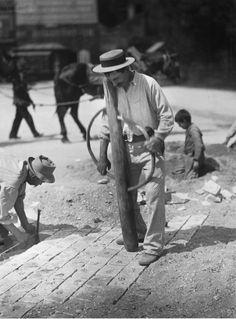 Superbe dameuse à pavés, paveur en train de mettre son cordeau, joints comblés avec un sable grossier, et un enfant au travail...