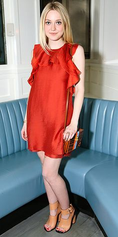 Last Night's Look: Love It or Leave It? Vote Now! | DAKOTA FANNING  | wearing a red, ruffled dress with a raw hem, an Edie Parker clutch and tan open-toe shoes at a party celebrating the opening of The Conscious Pop-Up Shop, hosted by H&M and Olivia Wilde in N.Y.C.