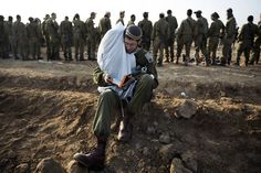An Israeli soldier holds Torah scrolls as he conducts morning prayers at an Israeli army deployment area near the Israel-Gaza Strip border in preparation for a potential ground operation in the Palestinian coastal enclave, November 19, 2012. (Menahem Kahana/AFP/Getty Images)