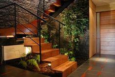 Un sector dentro de la casa con plantas, piedra, y madera