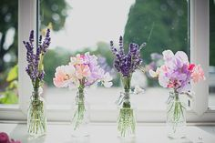 lovely purple flowers in glass jars are the perfect wedding decor — especially for a spring or summertime wedding!