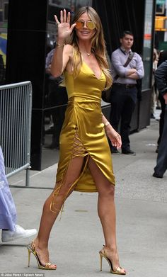 Golden gal! Heidi Klumparaded her endless stems in a golden yellow dress that featured a ...
