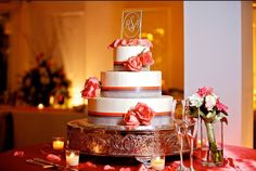 Lovely 3-tier round cake with coral color ribbon and roses. Andrea & Rich in The Shoreline Room | The Yacht Club at Marina Shores #Wedding #VirginiaBeach #marina #boats #docks @The Yacht Club at Marina Shores