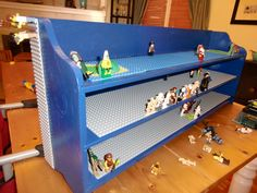 Take an old, worn out spice rack, nail on a sturdy back, prime it, paint it, and glue on some custom Lego boards. From trash to treasure.
