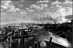 Henri-Cartier Bresson - Désordre matériel, horizon centré (Contraste Masse noire/blanche) ville à l'arrière plan. Photo post-apocalyptique.
