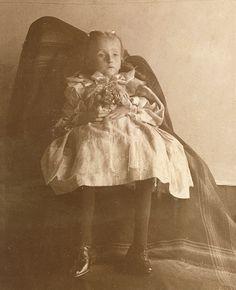 Mother under blanket holding up deceased daughter...