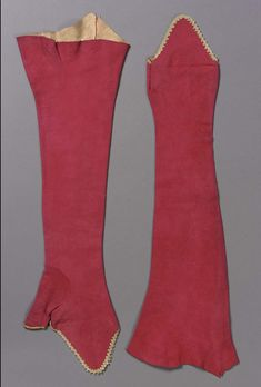 Pair of mitts, Italy or France, late 18th century. Crimson soft leather, trimmed with cream colored silk braid around hand and thumb. Cream colored taffeta, worn and cracked, lines flap over hand.