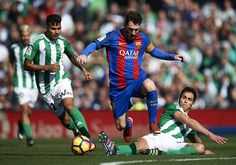 Lionel Messi of FC Barcelona (C) competes for the ball with Asia Mandi of Real Betis Balompie (R) and Matias Nahuel of Real Betis Balompie (L) during La Liga match between Real Betis Balompie and FC Barcelona at Benito Villamarin Stadium on January 29, 2017 in Seville, Spain.