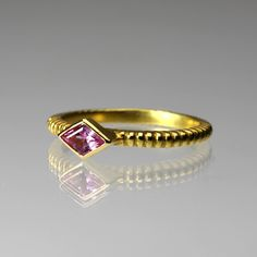 Vibrant feminine color is the story with this Barbara Heinrich ring! Handcrafted from 18K yellow gold, the ridge band holds a bezel set kits shaped pink sapphire. Meant to be stacked, and also oh so pretty worn solo - this ring is versatile and uplifting!<br><br>Sapphire = 0.23 carats<br>Band measures 2mm wide<br>Stone measures 4.5 x 6.5mm<br>Size 6.5