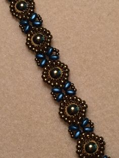 Hand woven. Gold round beads, gold seed beads and blue Super Duos. Magnetic closure. Measures about 7 1/2 inches long and 1/2 inch wide.