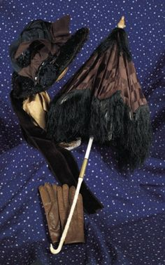 """Antique Accessories for Dressing Dolls~~~Suitable for larger dolls, including bonnet with brown velvet brim, richly crusted black bead trim on back, decorations of brown velvet and silk, 5"""" inside head width; 23"""" L. umbrella with bone- carved handle terminating in dog-head handle, hinged closure with brass entrapment, brown silk cover with long black silk fringe; and 5"""" brown leather gloves with snap wrist closures. Excellent condition. Late 19th century."""