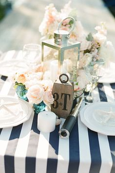 Cute- a bluish tinted vase with blush roses, with a navy and white table runner and lantern ??