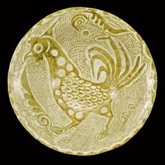 AN ABBASID LUSTRE BOWL, IRAQ, 9TH-10TH CENTURY of shallow rounded form with everted rim, supported on a short foot, decorated in a golden lustre with a monumental cockerel and two split-palmettes reserved on a dotted ground, scalloping to rim, the reverse with six-roundels with foliate and dot motifs 24cm. diam.