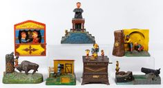 """Lot 467: Reproduction Cast Iron Mechanical Bank Assortment; Seven items reproduced from the """"Book of Knowledge"""" collection including Punch and Judy, the Frog Bank, the Organ Bank, Uncle Remus and the Magician Bank"""