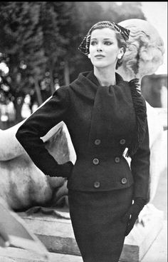 """1954-55 Model in black wool suit called """"Arsène"""" with fringed collar that forms a jabot by Nina Ricci"""