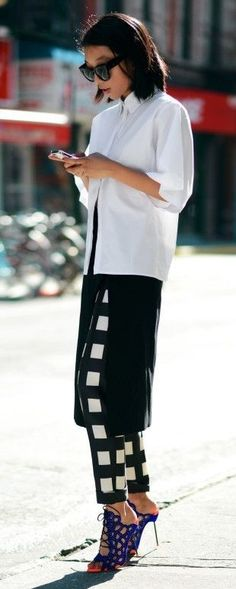 White Blouse, Thigh Split Black Skirt On Graphic Check Pants and Black Heels For A Modern And Urban Matching Black And White Outfit