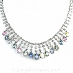 A rare and unusual array of natural (unheated), pastel colored, Burmese sapphires dance below a a sparkling 7.50 carat diamond necklace in platinum. Fifteen sapphires totaling 33 carats range in color from diamond white to royal blue, with shades of pink, yellow, aqua and green in between. A beautiful one-a-kind necklace for a beautiful one-of-a-kind lady. 15 inches in length.