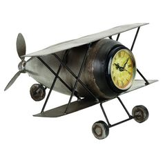 Add travel-chic appeal to your living room or library with this iron table clock, showcasing an airplane silhouette and antique-inspired face.