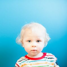 I photographed this 1-year-old sweet little boy on a blue background.