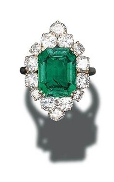 A FINE EMERALD AND DIAMOND CLUSTER RING, BY CARTIER   Set with a rectangular-cut emerald weighing 7.23 carats in a circular-cut diamond by BarbLT