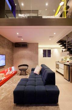 Sala de estar com sofá azul marinho e detalhes em vermelho
