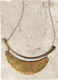 The Crescent Moon Necklace suspends a hammered brass pendant from a gold-fill chain.