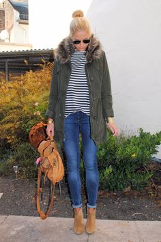 military parka with striped top, rolled up jeans, brown boots and brown leather backpack