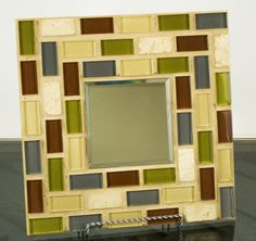 Add depth and light to any room with this stylish 12x12 blue and brown mosaic mirror. Glass tile and sand colored grout are brought together to create this one of a kind work of art. Place it on an easel or hang it on a wall. Its both beautiful and functional. I love the look of this mirror so much I have one in my own home. Its simple and elegant and the neutral colors go great with any style decor. Actual size is 12 x 12 Mirror size is 4 x 4