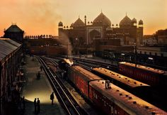 Photo by @stevemccurryofficial // I photographed this image at Agra Fort Station Agra India where an attendant adjusts a ventilator on the top of a train carriage. The domes and minarets of the Jama Masjid a mosque completed in 1648 under Mogul Emperor Shah Jahan are visible in the late afternoon light. by natgeo