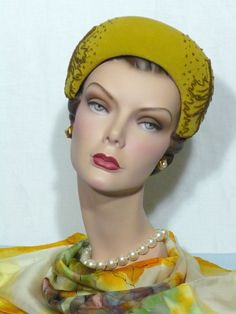1950's sculpted hat by Hattie Carnegie (front view) | The golden (with the very slighted hint of green) wool felt has a very soft velour finish | The shape is simple but exquisite:a rounded crown with a sculpted roll around the face | On each side of the hat are applied felt leaves which are outlined with small brown glass beads. There are glass beads scattered around the leaves