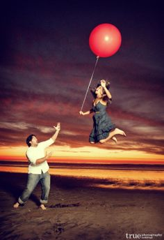 Fiancée about to fly away with her red balloon - fun and creative engagement shot on San Diego beach