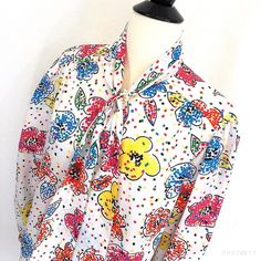 Vintage bow blouse Vintage pop of color! Size and frabric tags removed but most likely 100% polyester size medium. Adorable bright print bow blouse. Small stain on front in 2nd pic not seen if tie is worn long. Style with a pencil mini skirt as shown. Puff sleeves and pearl round buttons. 24 inch sleeves 26 inches shoulder to hem. Square hemline. Decent vintage condition. A few small snags and the small stain. Vintage Tops Blouses