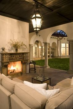 Mediterranean-style covered loggia with stone columns and fireplace