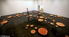 Walking on water: Sooz Moon, 28, steps from log to log as she visits the installation at Bristol's Arnolfini