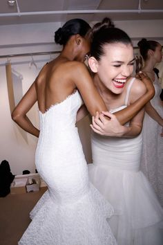 """Backstage at the Fall 2014 Amsale show, the models share a laugh. The model on the left is wearing the """"Deyvn"""" strapless fit to flare gown with ruffle detail and corded lace. The model on the right is wearing the """"Sawyer"""" tulle rouched bodice fit to flare gown with straps and corded lace top bodice."""