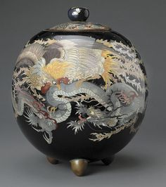 A large cloisonné enamel jar and cover Meiji period The slightly faceted sides of the globular body decorated with battling phoenix and dragon in bright polychrome enamels on a mirror-black ground, a beaded band encircling the fitted lid with a pattern of overlapping brocade panels below a knob scattered with butterflies, all raised on three short gilt metal supports