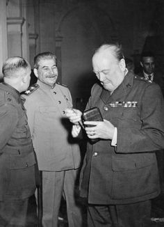 THE YALTA CONFERENCE, FEBRUARY 1945. Winston Churchill takes a fresh cigar from a case as Joseph Stalin looks on, smiling, during a break in the Yalta Conference.