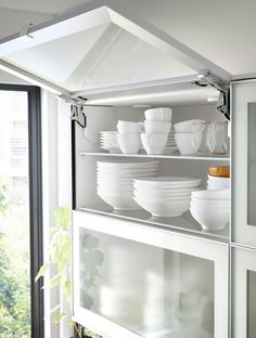 Open horizontal glass wall cabinet door revealing dishes Remind me of my Gran's kitchen in Cambridge. Ikea White Kitchen Cabinets, Aluminum Kitchen Cabinets, Glass Kitchen Cabinet Doors, Aluminium Kitchen, Kitchen Soffit, Ikea Kitchen Design, White Kitchen Decor, Ikea Cabinets, Glass Cabinets